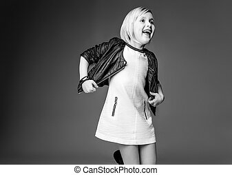 cheerful stylish child in white dress on grey having fun time