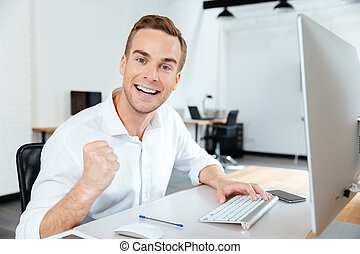 Cheerful successful young businessman celebrating success in office