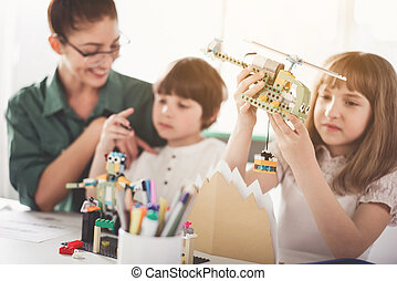 Cheerful teacher and kids playing with toys