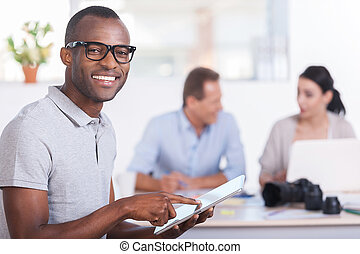 Cheerful team leader. Handsome young African man working on digital tablet and smiling while two people working on background