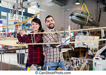 Cheerful team of aircraft enthusiasts holding sports airplane models in workshop