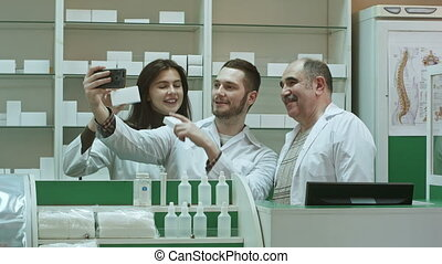 Cheerful team of pharmacist and interns take selfie via smartphone at workplace