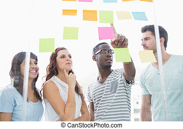 Cheerful teamwork pointing sticky notes and interacting in...