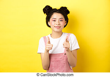 Cheerful teen asian girl pointing fingers at camera and smiling, encourage or invite you, making compliment, praise nice work, standing on yellow background