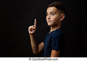 teen boy pointing up over black background
