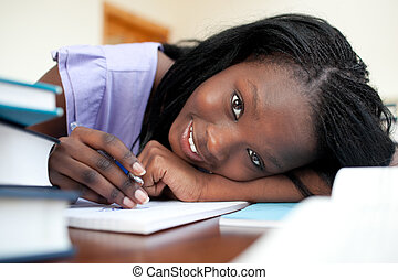 Cheerful teen girl doing her homework