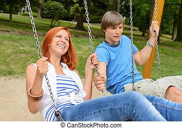 Cheerful teenage couple on swing in park