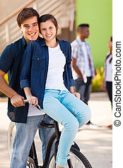 teenage couple riding a bicycle