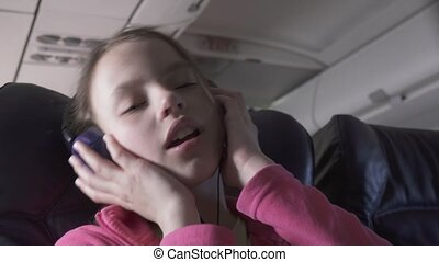 Cheerful teenage girl listens to music on headphones in the cabin of plane while traveling