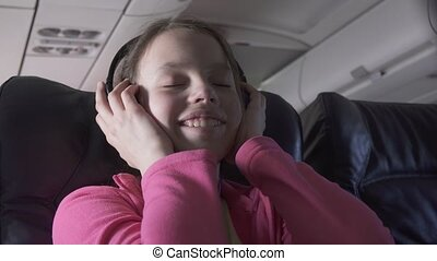 Cheerful teenage girl listens to music on headphones in the cabin of plane while traveling stock footage video