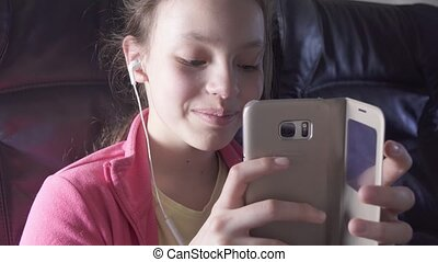 Cheerful teenage girl plays a game on smartphone in the cabin of the plane while traveling stock footage video