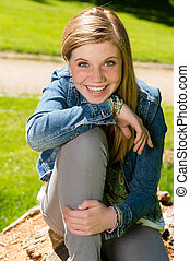 Cheerful teenage girl sitting in the park