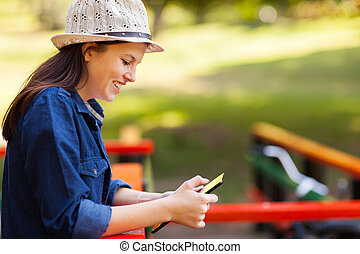teenage girl using tablet computer outdoors