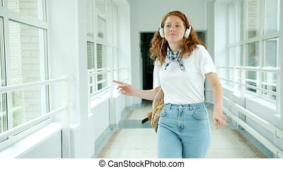 Cheerful teenager in headphones enjoying music dancing in school hall having fun