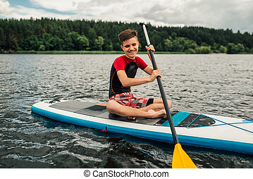 cheerful teenager sitting on a sap surf   and rowing with an oar
