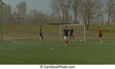 Cheerful teenagers playing soccer on sports field