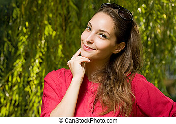 Cheerful thinking young brunette woman.