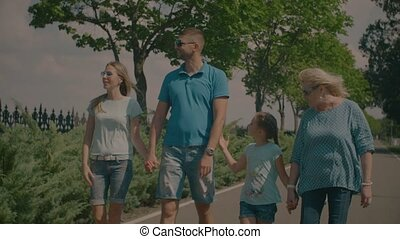 Cheerful three generation family walking outdoors - Cheerful...