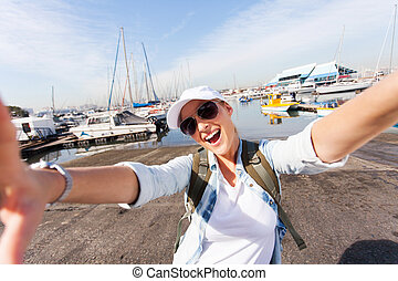 cheerful tourist taking selfie by wharf