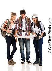 cheerful tourists looking at map on white background