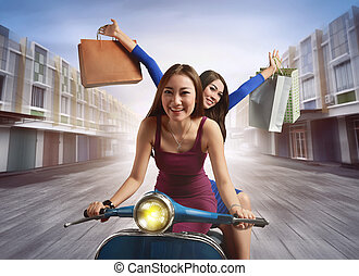 Cheerful two young asian woman with shopping bag riding a scooter