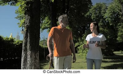 Cheerful volunteer walking in the park with a senior man
