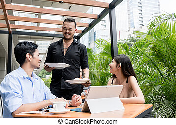 Cheerful waiter bringing two plates of food to the table of a young couple