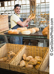 Cheerful waiter in apron holding baguettes
