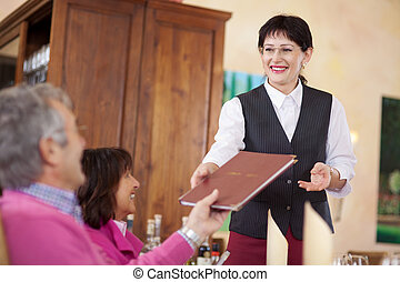 cheerful waitress passing the menu to guest - cheerful...