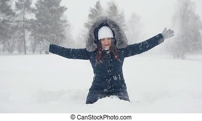 Cheerful walks in the winter park. Young woman playing with snow in a snowdrift