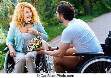 Cheerful wheelchaired woman getting a bunch of flowers
