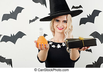 Cheerful witch with Halloween presents