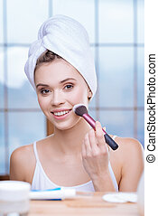 Cheerful woman applying powder and smiling