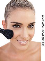 Cheerful woman applying powder on her cheeks