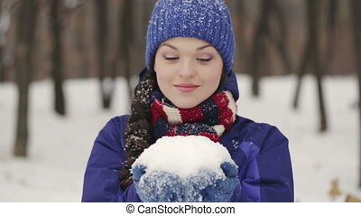 Cheerful Woman blows on snow