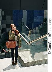 Cheerful woman calling on phone