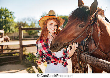 Cheerful woman cowgirl giving food to horse on ranch - young...