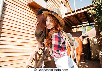 Cheerful woman cowgirl standing and hugging her horse on...