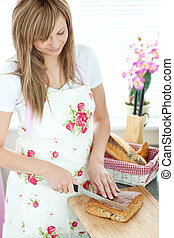 Cheerful woman cutting bread in the kitchen