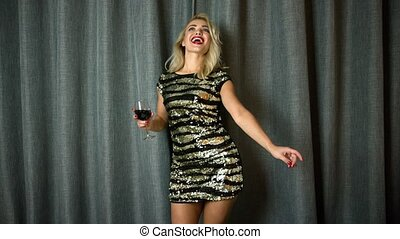 Cheerful woman dancing with red wine