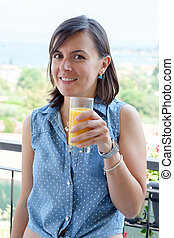 Cheerful woman drinking a glass of orange juice