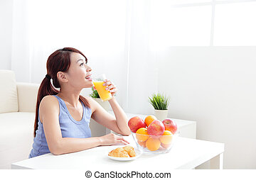 Cheerful woman drinking an orange juice