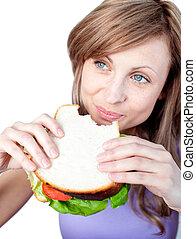 Cheerful woman eating a sandwich