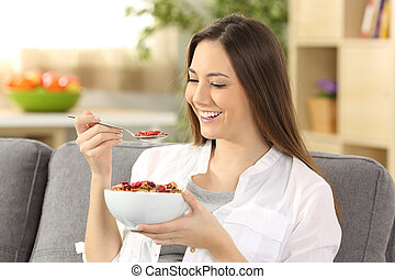 Cheerful woman eating cereals at home