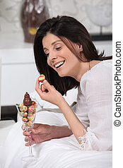 Cheerful woman eating Easter eggs