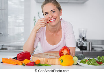 Cheerful woman eating vegetables