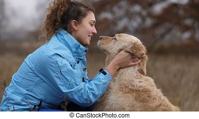 Cheerful woman embracing her cute dog outdoors