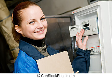cheerful woman engineer checking technical data of heating system equipment in a boiler room