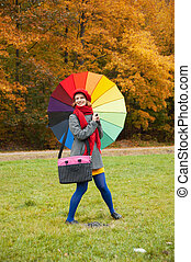 Cheerful woman enjoying autumn day in park