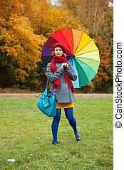Cheerful woman enjoying autumn day in park